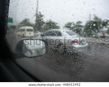 Road view through car window blurry with heavy rain, Driving in rain, rainy weather #448411492