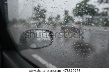 Road view through car window blurry with heavy rain, Driving in rain, rainy weather #478890973