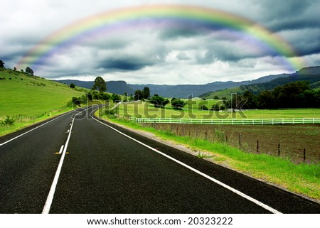 Road winding through farm land and a gorgeous rainbow