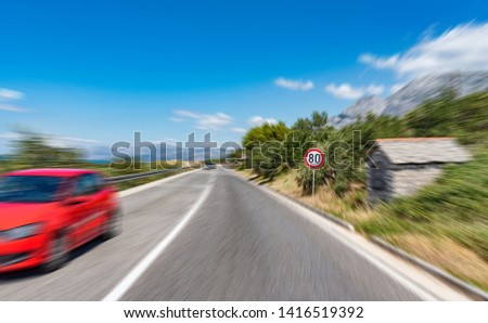 Road with a warning sign outside the city and a red car in motion. Added Motion Blur. #1416519392