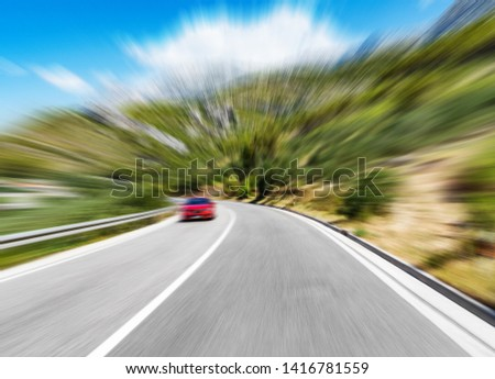 Road with a warning sign outside the city and a red car in motion. Added Motion Blur. #1416781559