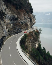 Road with beautiful views of the lake and mountains of Switzerland. A red car is driving on a winding road near Interlaken in the Swiss Alps.