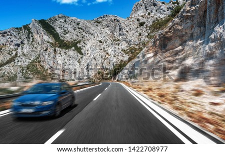 Road with blue car in motion. Added Motion Blur. #1422708977