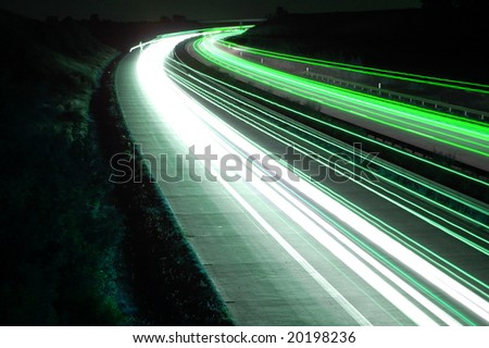 road with car traffic at night and blurry lights showing speed and motion - stock photo