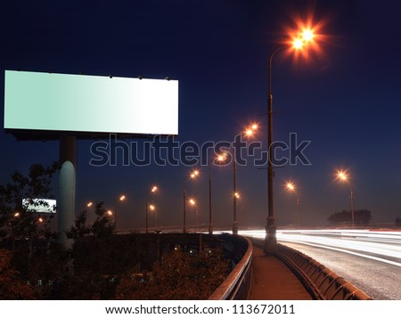 Road with lights and large blank billboard at dark night in city.