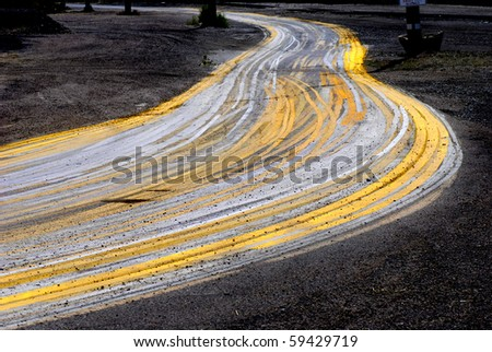 Road with painted yellow lines and big curve or turn