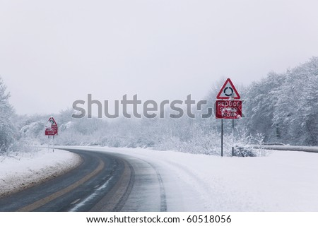 Road with Reduce speed now sign during snow fall of winter 2010