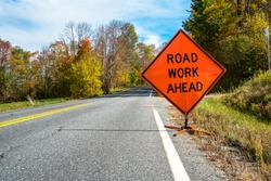 Road work ahead road sign telling motorists to be alert as they are entering a contruction area on a country road on a sunny autumn day. Beautiful fall colors.