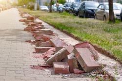 Road work, curb replacement, urban landscape edging. Broken sidewalk border. Damaged brick sidewalk border, pavement edges.
