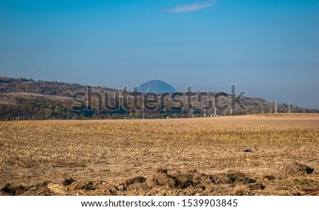 road worked after the vegetables were harvested with a blue sky above and the mountain blurred on the back near Brasov Romania