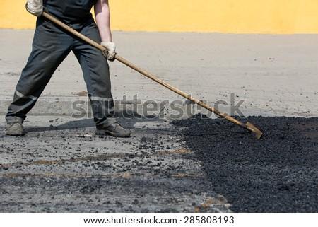 Road worker leveling fresh asphalt during asphalt pavement repair or construction works