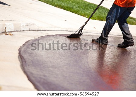 Road Worker Resurfacing Street with Hot Tar.