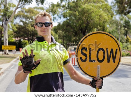 Road worker slows traffic with hand and sign