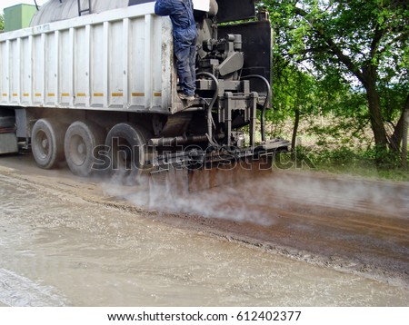 Road worker spraying bitumen emulsion with the truck