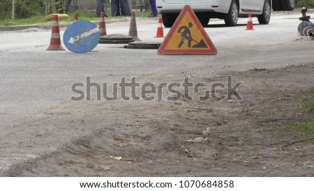 road workers repair the road, cones in foreground #1070684858