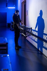 Roadie carrying a big truss support to the stage, casting a shadow on the wall,
