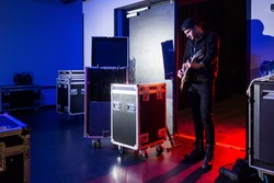 Roadie playing guitar backstage, standing near the stage entrance, surrounded by flight cases, containing equipment.