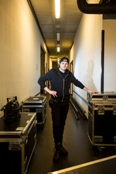 Roadie standing backstage leaning against a flight case in a hallway