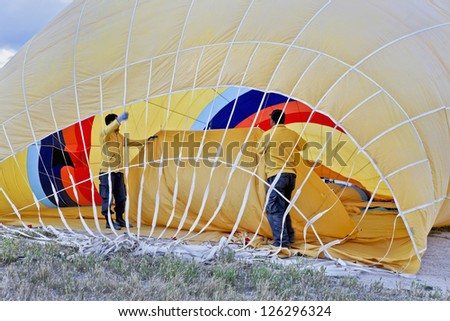 Roadies working inside a yellow hot air balloon making ready for a flight for tourist passengers in Cappadocia Turkey