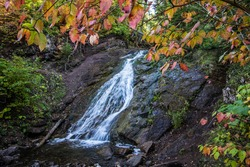 Roadside Northern Michigan Waterfalls In Autumn. Jacob's Falls is a roadside waterfall in Keweenaw County on M 26. Shot in horizontal orientation with autumn leaves framing the falls.