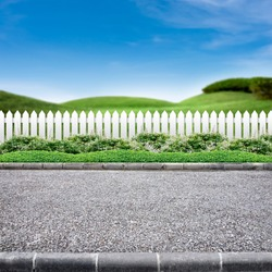 Roadside view  and white fence on green landscape background