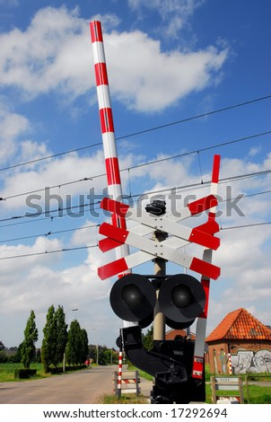 Roadsign for railway crossing in rural environment with blue sky background