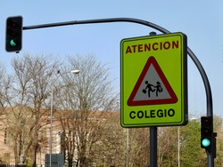 Roadsign protecting kids from cars hazard on the street of Lavapies district of Madrid, Spain. Word on traffic sign in Spanish means