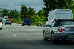 Roadster in the traffic on Italian highway by summer