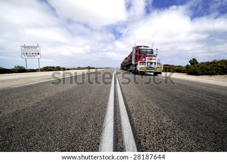 Roadtrain in Nullarbor desert,Australia. At left side sign with quarantine restrictions.