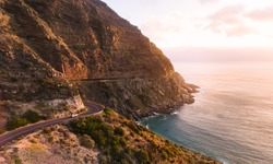 Roadtrip in beautiful landscape. Car driving on the famous Chapmans Peak Drive stretch close to Cape Town, South Africa.