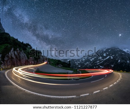 Roadway in mountains under starry sky, Exposure lights of roadway traffic among dark mountains in starry night with amazing skyline in time-lapse