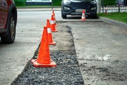 Roadwork, driveway repair, prepare for laying new asphalt. Damaged asphalt road surface repairing. Preparing for patch works. Repair pothole in asphalt pavement, road work warning cones.