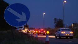 roadworks cones flashing on UK motorway at night with traffic passing