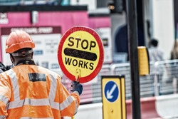 Roadworks signal with worker standing.