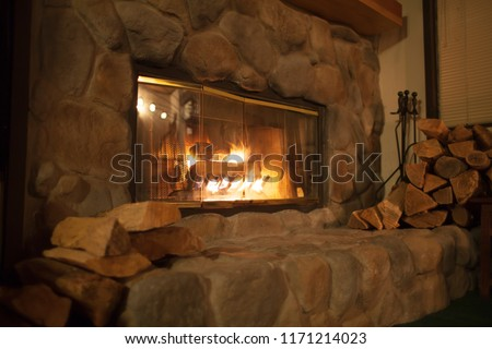 Roaring fire in an arched stone fireplace  #1171214023