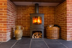 Roaring fire inside wood burning stove in brick fireplace with basket of cut wood ready for burning