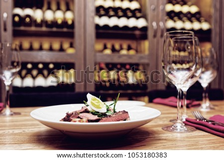 Roast beef appetizer on table, wine racks in blurred background, toned picture