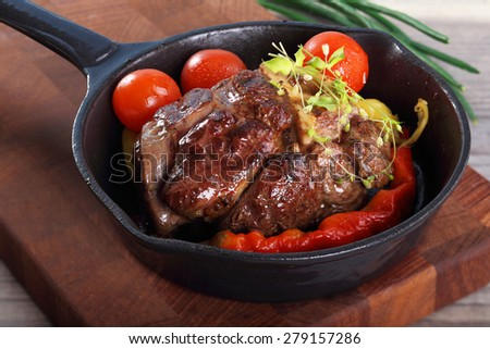 roast beef in a frying pan with vegetables