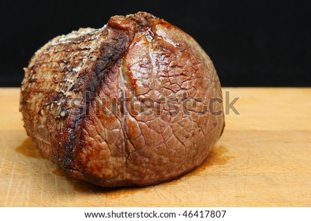 Roast beef joint on wooden carving board.