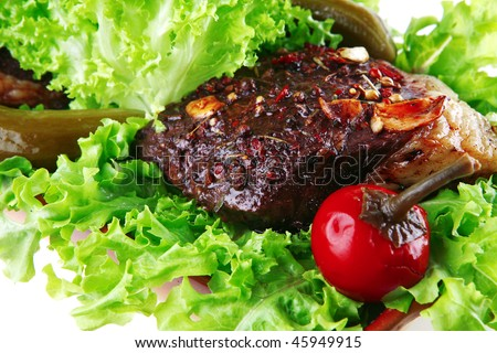 roast beef meat on green salad over white