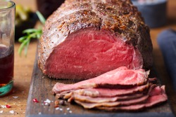 Roast beef on cutting board. Wooden background. Close up.