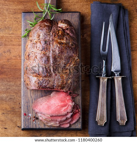 Roast beef on cutting board. Wooden background. Top view. #1180400260