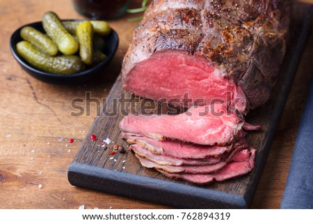 Roast beef on wooden cutting board with pickles.