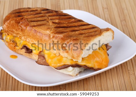 Roast beef sandwich covered with melted cheese on grilled French bread