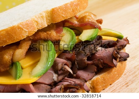 Roast beef sandwich with cheddar cheese, sliced avocado, and bacon strips.