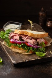 Roast beef sandwich with tomato, onion, lettuce and mustard sauce on dark background. Delicious healthy lunch with meat, hearty food