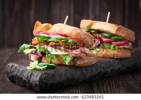 Roast beef sandwiches with fresh salad, vegetables, cheese and mustard sauce on rustic background