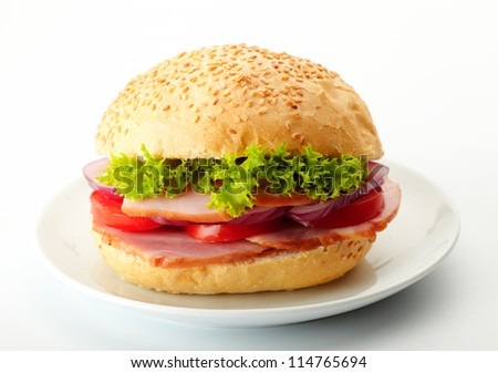 Roast Beef Sandwiches with Lettuce, Tomatoes and Red Onions on a white plate