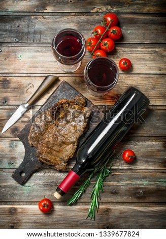 Roast beef steak with red wine. On a wooden background. #1339677824