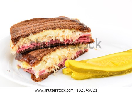 Roast beef; swiss cheese and sauerkraut grilled on wheat bread on white plate with white background and served with bread and butter pickle.